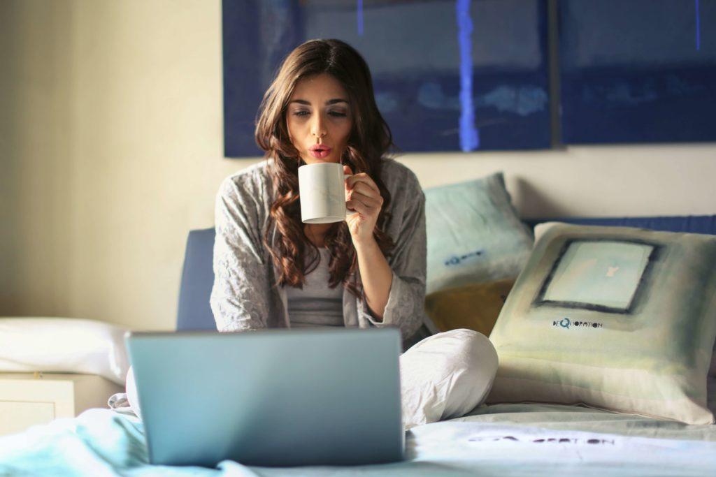 コーヒーを飲みながらパソコンをしている女性